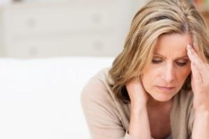 Frau mit Erkältung hält sich den Kopf